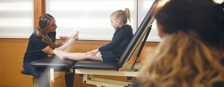 Podotherapeut legt uit aan een kind