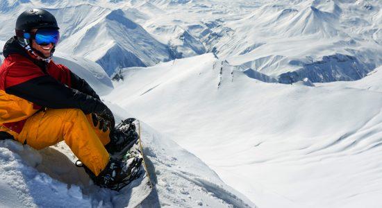 Snowboarder zittend in de sneeuw